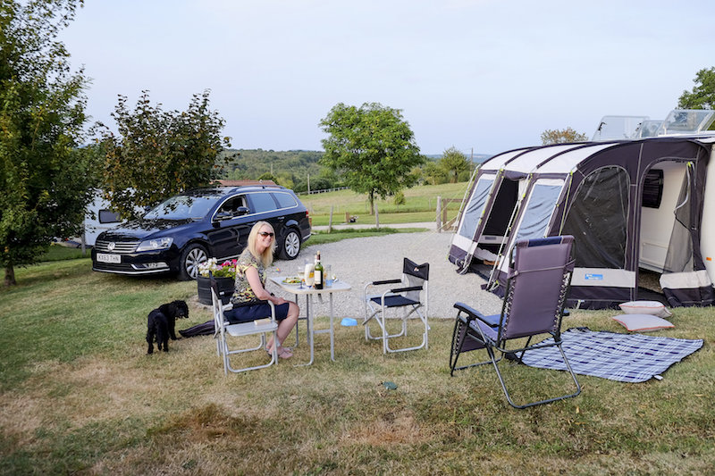 a lady outside her caravan with her dog and a bottle of wine