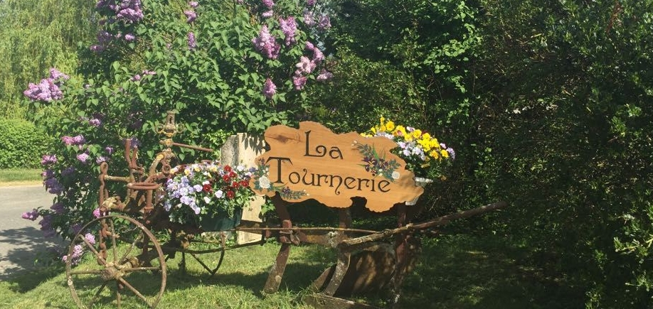 "The sign welcomes you to the entrance of the site: ""La Tournerie"". It is hung from an old plough and is decorated with flowers"